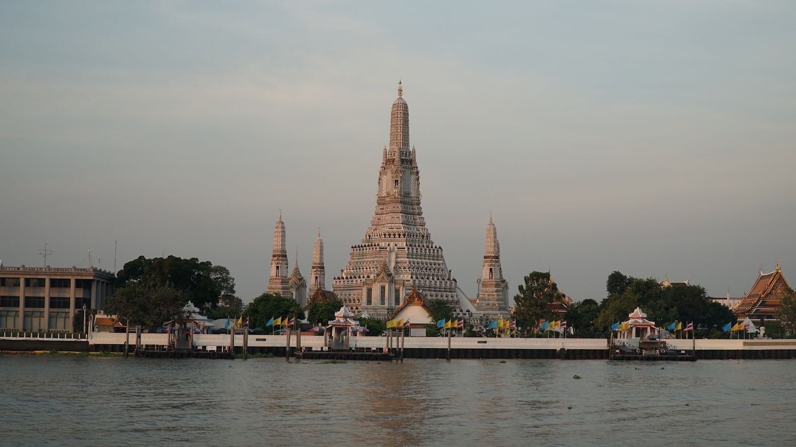 Wat Arun (Temple of Dawn) one of the most recognizable templates in Bangkok. Taking this photo was quite the struggle. The template is situated on the banks of the river. Across the water, the entire opposite bank is lined with residential homes or shops and businesses that weren't open yet. I wanted a shot from across the river and I ran around to find a section of the riverbank that was open to the public but never found it. I wanted to photograph the temple before the sun completely rose and was running out of time looking for a public view. I ended up sneaking into the patio of a boutique coffee shop to take this photo, until the owner came by to open the shop and kicked me out.